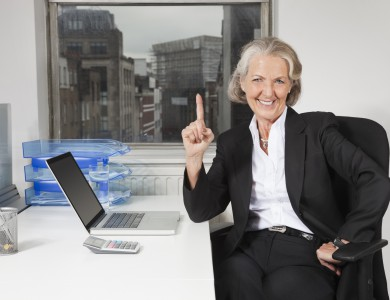 Portrait of senior businesswoman with laptop at desk in office